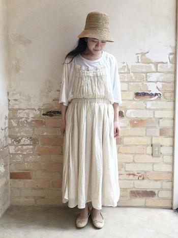 淡いオフホワイトのギャザーエプロンワンピース。白とベージュでまとめたナチュラルで女の子らしい着こなしです。