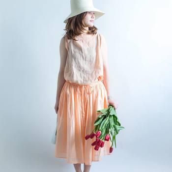 透け感のある優しいトーンのオレンジ色のワンピース。淡いカラーは、暑い夏でも涼し気に女性らしく着られますよ。