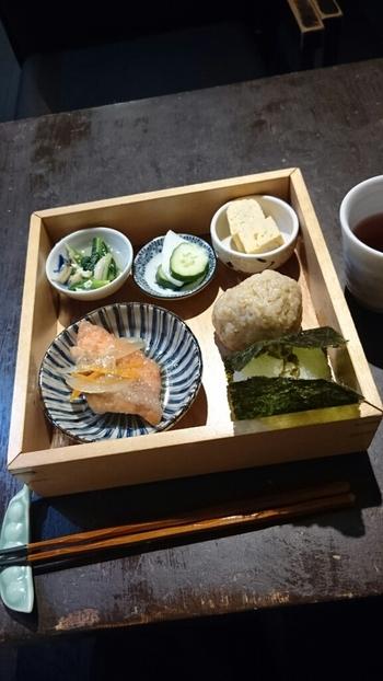 木箱に入ったランチセットには、玄米のおにぎり、本日のおにぎり、さらに利さく特選おかずが。利さくでは、もっとも美味しい状態のおにぎりを提供したいという想いから、作り置きせず、注文が入ってから握り始めているんです。