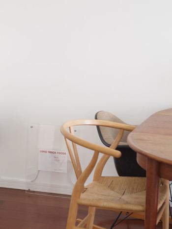 そこで、無印良品の「アクリルフレーム」に、ショップのフライヤーを入れたもので隠したのがこちらです。白い壁に馴染んで、目立たなくなっていますね。