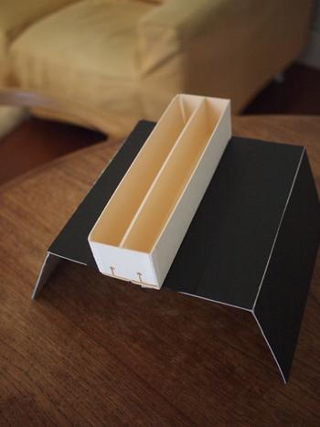 最初はカゴにざっくりと入れていたところ、ごちゃごちゃになってしまったので、「住所のある収納」を、と手作りしたものがこちら。  カゴの中で充電したいものの大きさに合わせて、しっかりした厚紙をカットして作っています。コードを通しておく穴もちゃんと空いていますね。