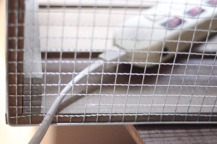 DIYで作成した「キャベツボックス」を二段に仕切り、網の部分をカットしてコンセントタップを通します。ボックスの上部に設置したコンセントタップを隠すために、野地板(板材)を蝶番で留めつけて。  これでスマホを取り出す時もスムーズ。考えられていますね!