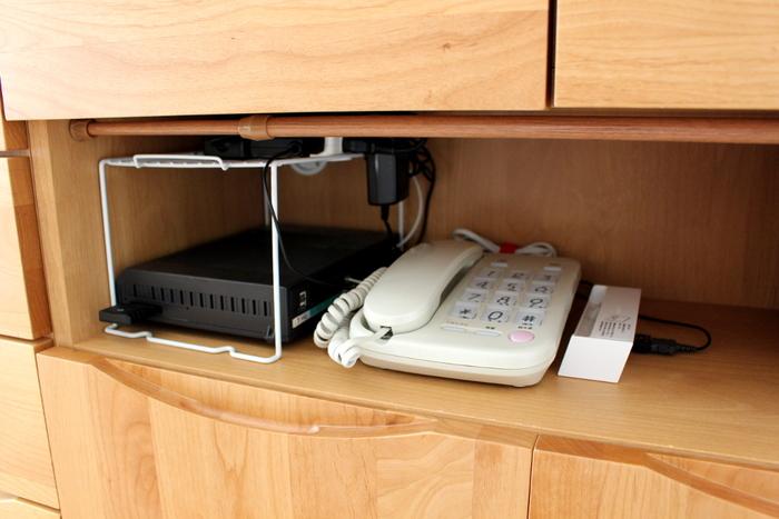 カーテンの奥には固定電話機も。電源タップは100均のラックの上に浮かせて収納して、熱対策を。目隠し用のカーテンは好きなファブリックを100均の突っ張り棒にかけるだけなので、とても簡単ですね!