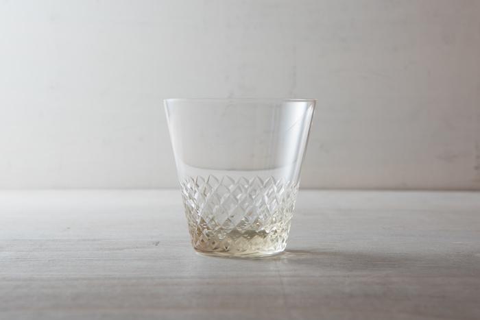 """こちらも、廣田硝子のもの。江戸切子の""""あられ紋""""を施した、熟練技が光るグラス。淡い琥珀色は、レトロさを残しつつも落ち着いた印象です。お水を入れると、切子模様に光が反射して、きらきらと美しく輝きます。"""