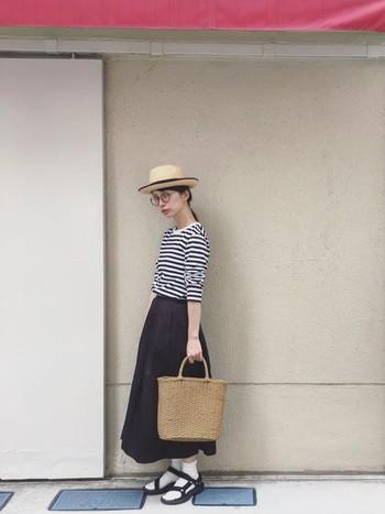 つばが広めのカンカン帽と大きめのカゴバック。足元は、テバと白靴下の組み合わせでカジュアルに。爽やかな着こなしはリゾートスタイルとしてもおすすめです。