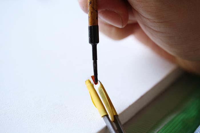 打って変わって、ガラスに細かい筆使いで丁寧に金彩(液状にした金)を施す繊細な作業。この後、600度ほどの熱を加えることで金液の不純物がとび、ガラスに薄い金の膜が定着します