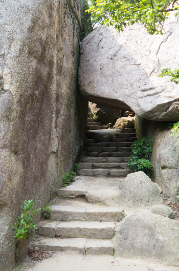 こちらは山頂付近にある巨大な岩で、通称「くぐり岩」。このトンネルを抜ければ、ゴールは目の前です!大きな岩が集まる不思議な山頂と、眼下に広がる瀬戸内海の景色を思う存分堪能しましょう♪