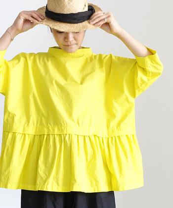 スタンドカラーと裾のギャザーが素敵なコットンブラウス。たっぷりしたシルエットで一枚で着るだけで様になります。きれいなイエローがよく映えます。