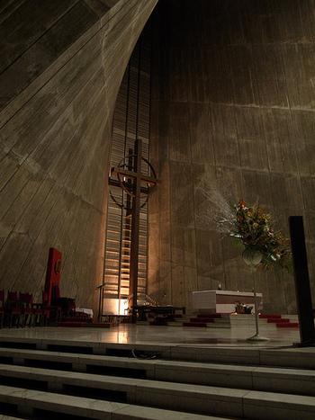 特徴的な形状の空間は、それだけで私たちの知る教会の印象とはずいぶんと異なります。 打ちっぱなしのコンクリートがみせる表情もまた、静謐で厳かな空気を作り出す一因なのかもしれません。