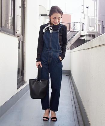 濃いめのデニムサロペットに黒のタイトなカットソー、小物と靴も黒で統一したシックなワントーンコーデです。首に巻いたスカーフがポイントに効いています。