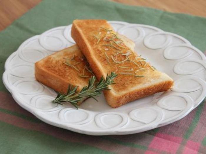 ローズマリーバターを、パンに塗ってからトースト。バジルでもパセリでもオレガノでも、同じように作ることができます。さわやかなハーブトーストを朝食に