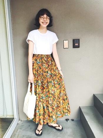 レトロなイエローのプリントがかわいい、ボリュームたっぷりのロングスカート。 Tシャツやバッグは白の無地を合わせて、スッキリと。 ロングスカートは重くなりがちですが、足元をビーチサンダルにすることによって、ヌケ感ある大人のコーデになっています。