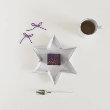 「華華火」という名の夏の羊羹を星形プレートにのせたら、夜空に咲いたお花のようになりました。羊羹の紫と合わせられた組みひものちょうちょ結びがとてもキュートです。