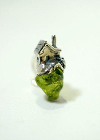 自然な形を活かしたカットのペリドットの上に、シルバー素材の建物(家)がデザインされた個性的なイヤリング。まるで緑の草原の上に家が建っているみたいですね。