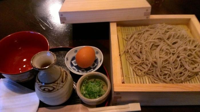 """店名の「銀そば」とは、""""蒸し蕎麦""""のことで、江戸期には一般的だった蕎麦の食べ方です。銀そばは、茹でたそばを木箱に並べ蒸し上げたものを温かい汁につけて頂きます。湯気ととともに蕎麦の香りが広がる「銀そば」は、モチっとして味わい深く、甘味の効いた汁とよく合うと評判です。【画像は、葱と生卵が付いた「銀そば」。】"""