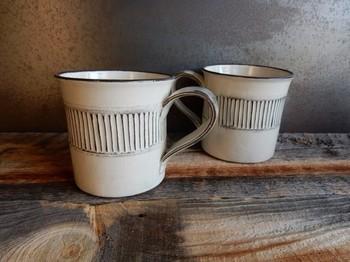 鎬(しのぎ)という技法で、模様が一本一本掘り出された拘りのマグカップ。  黒土の土台の上に白くなる土を被せ、口元に掛かっている白化粧を削り出すと、黒い部分が出てきます。  (しのぎマグカップ大サイズ(白))