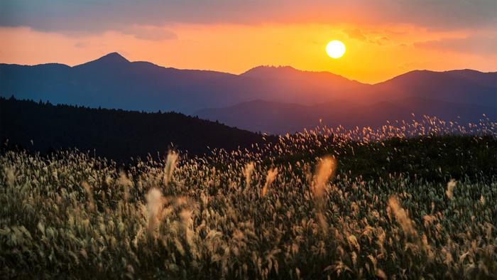 ダイナミックな山に沈む夕陽をバックに、ややパノラマ気味で撮影された一枚。自然の偉大さを感じますよね。