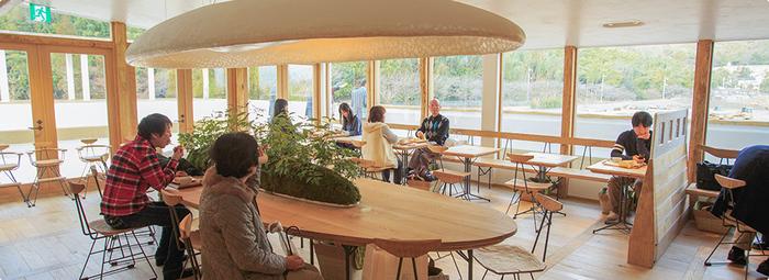 """クラブハリエに併設されたカフェでは、熟練の職人が焼き上げたほんのりあたたかい""""焼きたてバームクーヘン""""がいただけます。木のぬくもりあふれる店内は、テーブルから照明まで、内装は全て藤森照信さんによるデザインです。"""