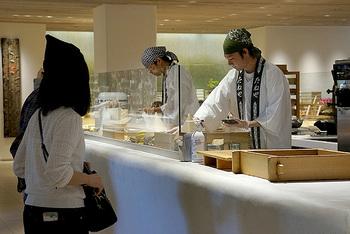 """和菓子売り場では、職人さんが目の前でお菓子を仕上げる「できたて工房」を併設しています。こちらのコーナーでは、たねやのあんこ&生クリーム、季節の果実を添えた""""生どらやき""""を販売。4月~9月中旬ごろまで、期間限定で""""どらソフト""""も販売中です。新鮮な卵を使った美味しい生地と、なめらかなソフトクリームのハーモニーをぜひご堪能ください♪"""
