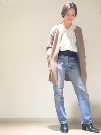 白トップスに色落ちデニム、シンプルな組み合わせにブーツと同色のサッシュベルトでハードさをプラス。ベージュのカーディガンで女性らしさもあり、シンプルなのにカッコイイ大人のデニムコーデの完成です。