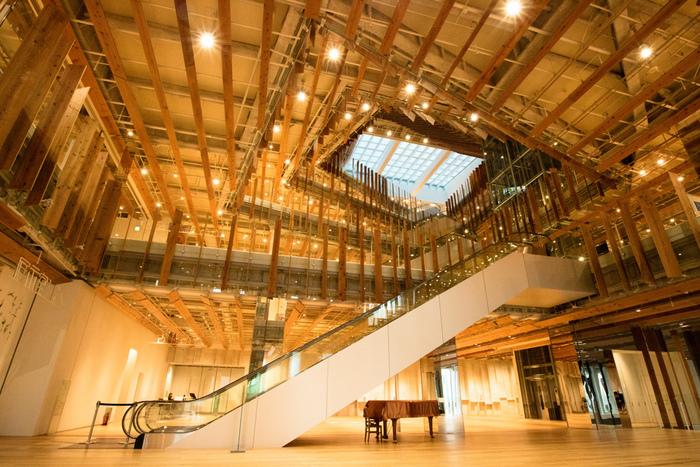 木が印象的な温かみのあるデザインの館内。建築家の隈研吾氏によって手がけられており、広々とした開放感のある美しいアート空間になっています。館内はフロアで分けるのではなく、同じ空間に美術館と図書館がある、ユニークな構造になっているのが特徴です。