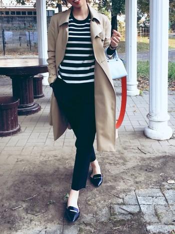 ボーダーカットソーにくるぶし丈のパンツ、さらにトレンチコートを羽織った、オードリー風のフレンチ・カジュアルな着こなし。