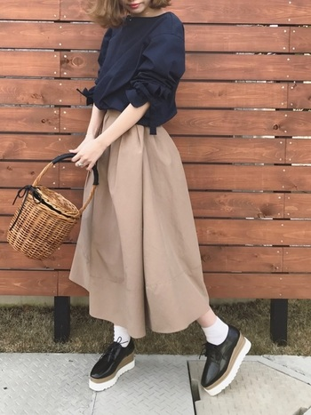 こちらは大人っぽく。紺の袖ギャザートップスにカゴバッグでレディな仕上がり。靴下×おじ靴で、品良くカジュアルダウンして。