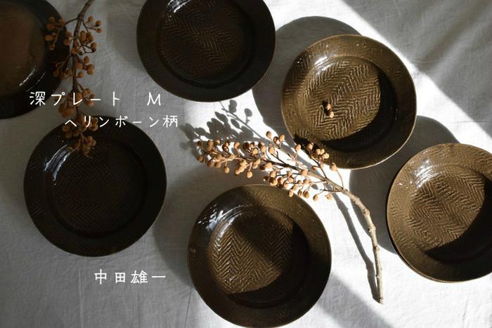 """北海道生まれの陶芸家 中田雄一氏。大学で陶芸を学んだのち、現在は金沢に拠点を移し活動しています。ヘリンボーンシリーズに新しくでたブラックオリーブ色。""""ヘリンボーン""""とは魚を開いたカタチに似ている独特の模様のことです。"""