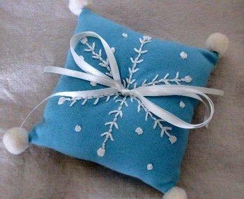 ウールの布に雪の結晶の刺繍とポンポン、リボンをつけたピンクッション。冬の手仕事にぴったりですね♪