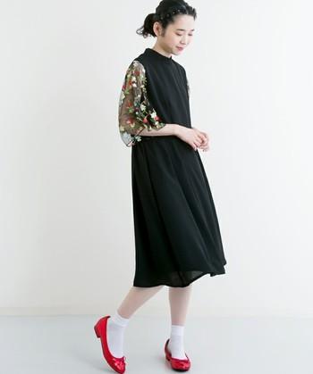 花柄&透け袖がシンプルなデザインのブラックワンピースを華やかな雰囲気に。靴下を合わせるコーディネートは結婚式には不向きですが、結婚式にはヒールとストッキングを合わせて、靴下スタイルは⼆次会にすれば、雰囲気も一変して◎