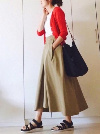 ボリュームのあるベージュのフレアースカートに、紅葉を思わせる赤のショートカーディガンが差し色になっています。