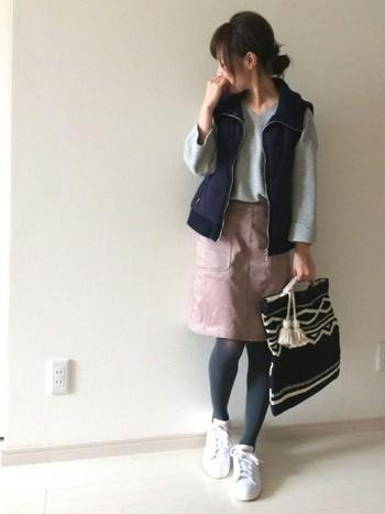 トレンドカラーのスモーキーピンクのスカートには、グレータイツがピッタリ。柔らかい印象はそのままに、コーディネートをまとめます。