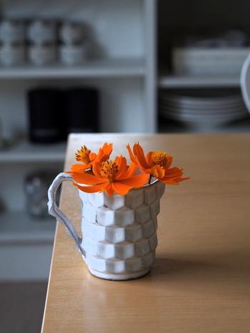 鮮やかなオレンジが美しいコスモスは、なんとお庭に咲いていたものだそう。可愛らしいお花のかたちに、ユニークなフォルムの白いカップがよく似合っています。