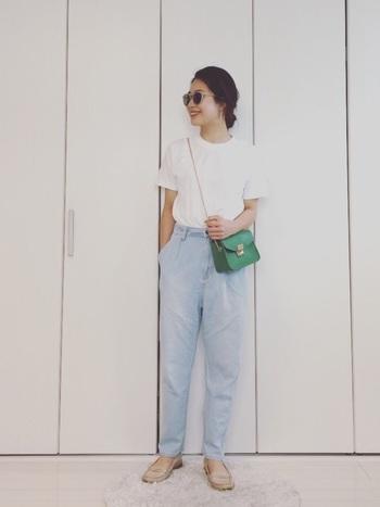 シンプルながらもおしゃれな雰囲気の白Tシャツのコーデ。グリーンの小ぶりなバッグがアクセントになっていて素敵。