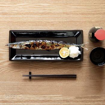 秋刀魚。  黒一色のお皿に、シンプルにのせました。端に大根おろしとすだちを。この定番の盛り方は、安定の美味しさを約束するテクニックです。