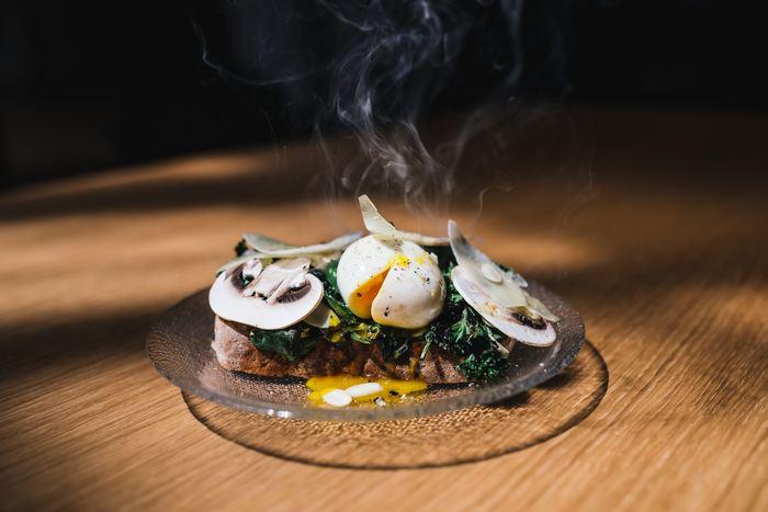 付け合わせのスライスマッシュルーム。  いつもなら白いお皿や色付きのお皿に盛り付けがちなお料理ですが、たまには透明のガラス皿を選んでみてはいかがでしょう?テーブルの木の温もりがお皿にも伝わってくるよう。ぜひお皿の上に小さな森を作ってみて。