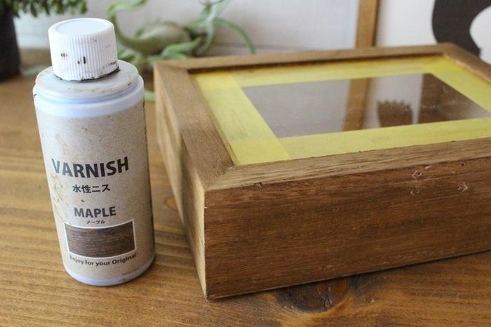 まずは、ケースに付いていた金具を外し、全体にセリアの水性ニスを塗ります。ふたの透明な部分にマスキングテープを貼っておくと、ニスが付くのを防ぐことができますよ。