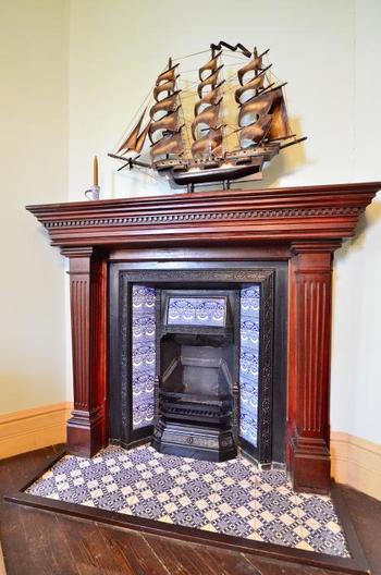 美しいタイルが敷き詰められた暖炉。模型の船も豪華な雰囲気を醸し出しています。