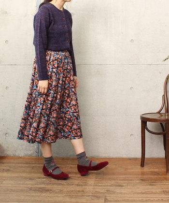 歩くたびに、ふくらはぎ辺りで揺れるミドル丈のフェミニンなスカート。赤と紫をメインにしたスタイリングは、何となくノスタルジックで可愛らしいですね。