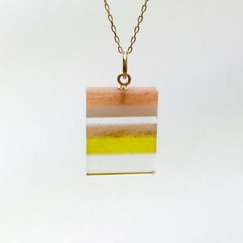 水晶やオレンジアベンチュリンを使用して作られたネックレス。天然石を重ね合わせ、色にこだわりながら研磨して作り上げた縞々模様がキュートです。  他にもブルー、パープルの3色展開となっています。