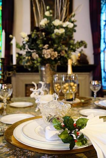 お皿に柊(ひいらぎ)を飾って華やかさと彩りをプラスしたテーブル。  真っ白なトナカイの置物がキュートなアクセントに☆