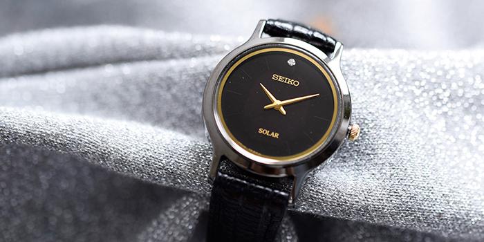 「SEIKO(セイコー)」のリザード型押しベルト ダイヤドレスソーラー腕時計。ブラックのフェイスにゴールドの針、そしてトップにひと粒のダイヤモンド。