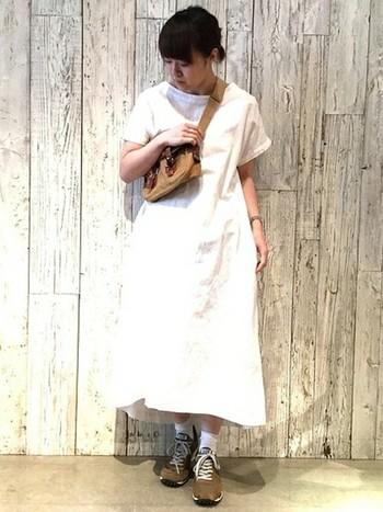 ベージュのバッグとスニーカーでカジュアルさと秋らしさを取り入れた白ワンピコーディネートです。