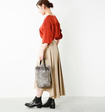テラコッタカラーのトップスに、ベージュのスカートを合わせたコーデ。ファーのバッグや黒色のショートブーツで柔らかな印象を引き締めつつ、季節感もしっかりアピールしています。