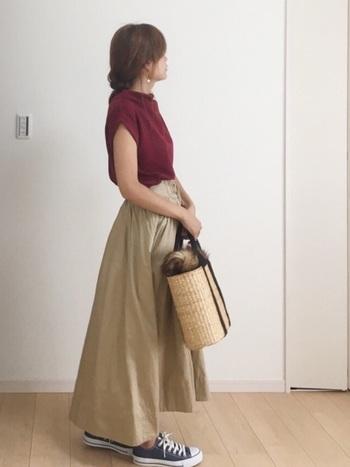 ボルドーのトップスに、ベージュのロングスカートを合わせたコーデです。足元はスニーカーでラフにまとめて、寒い日が続く時は羽織をプラスしてもOKなので、長く活躍できる着こなしですね。
