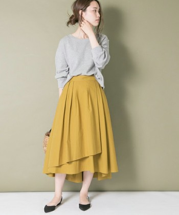 グレーのトップスに、マスタードカラーのフレアスカートを合わせた着こなし。ナチュラルで大人っぽさの強い配色ながら、トレンド感もばっちり取り入れています。