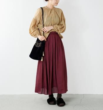 ベージュのブラウスにボルドーのロングスカートを合わせたスタイルです。かっちりしがちなブラウスに、あえてボルドーという強めカラーのスカートを合わせることで、秋の大人ナチュラルコーデに。
