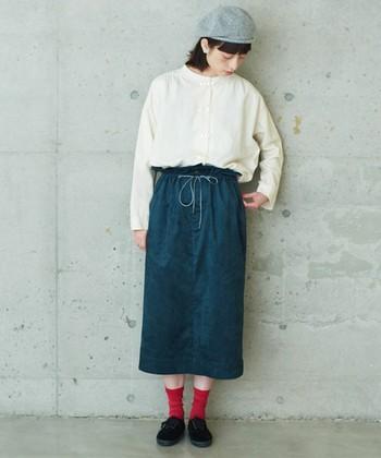 スウェード素材のスカートに、白ブラウスを合わせた着こなし。足元は赤の靴下を合わせて差し色に。バランスの取れたコーディネートです。