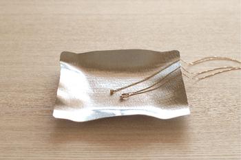 こちらはすずがみという、折り曲げることができる錫製のプレートです。アクセサリーのかたちに沿うようにかたちを変えることができます。