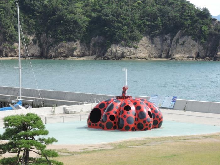 草間彌生 作 赤南瓜  直島の玄関口である宮之浦港に設置された赤南瓜。 スケールの大きさ、草間彌生ならではの鮮やかな色使いが目に飛び込んでくると、「アートの島・直島へきたんだ!」という気持ちになれます。中に入ることもできる体感型アートです。
